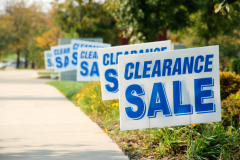 Picture of clearance sale signs in a row outside along a store sidewalk.